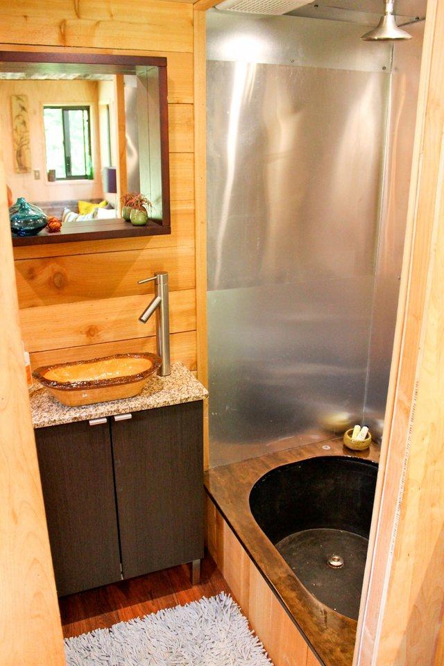 Sâu bên trong là phòng tắm có vòi sen và bồn rửa tay nhỏ nhỏ xinh xinh