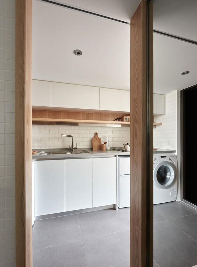 Máy giặt được chủ nhà đặt khéo léo vừa khít dưới gầm kệ bếp nấu.