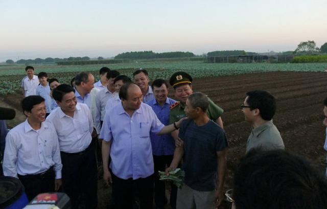 Rời chợ Long Biên lúc 5g30, Thủ tướng đã qua cầu Chương Dương đến cánh đồng rau của xã Văn Đức, huyện Gia Lâm và yêu cầu lái xe chạy thẳng ra bờ ruộng. Lúc này mới tờ mờ sáng, chỉ bắt gặp vài người dân đi làm đồng sớm, Thủ tướng hỏi anh Tới - một nông dân về quy trình làm rau sạch, các loại thuốc bảo vệ thực vật và phân bón mà nông dân này sử dụng - Ảnh: LÊ KIÊN