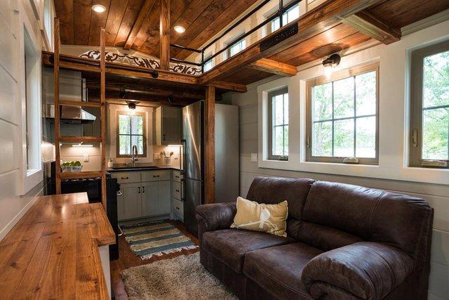 Phòng khách thiết kế đơn giản với chiếc ghế sofa dài và chiếc tủ gỗ nhỏ.