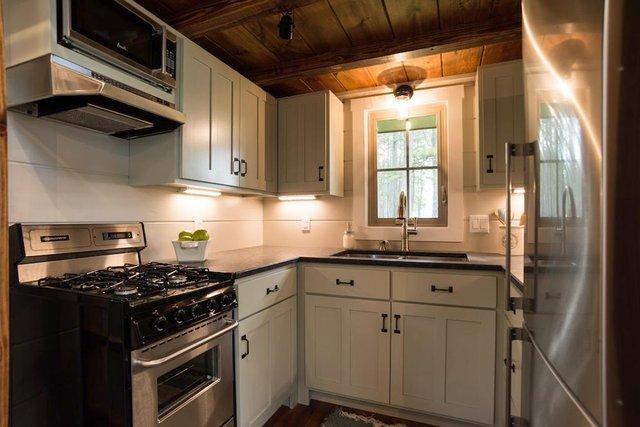 Bếp tuy nhỏ nhưng khá gọn gàng, ngăn nắp với hệ thống tủ kệ khép kín.