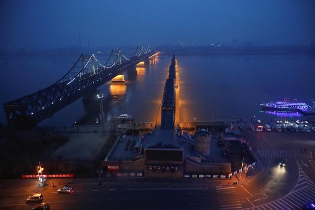Buổi đêm, chỉ có ánh sáng le lói phát ra từ thành phố Sinuiju, trái ngược với sự rực rỡ ở Đan Đông.