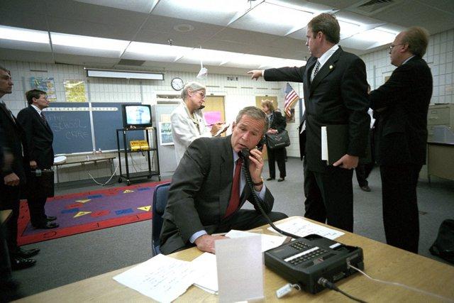 Dan Bartlett, phó trợ lý của Tổng thống, chỉ về phía bản tin được phát trên truyền hình về vụ tấn công ngày 11/9 khi Tổng thống Bush đang nghe một số cố vấn an ninh báo cáo tình hình qua tel. Được ra mắt năm ngoái, 15 năm sau vụ khủng bố chấn động địa cầu, một số bức ảnh cho thấy chính xác một số gì Tổng thống Bush làm khi nghe tin dữ.