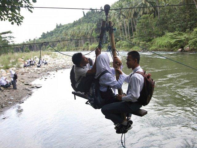 Học sinh đu mình trên các chiếc cáp treo tự chế để tới lớp ở Kolaka Utara, Indonesia.
