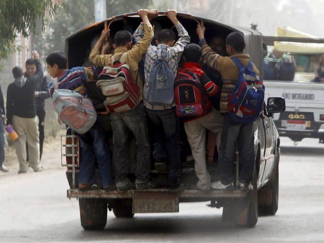 Trẻ em đánh đu trên xe xế hộp để tới trường ở Cairo, Ai Cập. Thay vì sử dụng xe buýt chuyên dụng, người ta dùng xe tải để đưa học sinh tới lớp bất chấp tai nạn có thể xảy ra bất cứ khi nào.