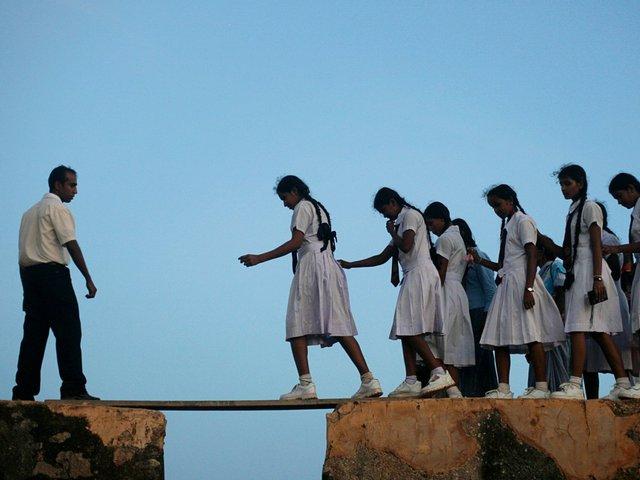 Những nữ sinh Sri Lanka phải bước qua tấm ván gỗ, nối giữa hai phần của bức tường cổ được thi công từ thế kỷ 16, để tới lớp.