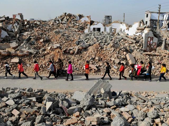 Trẻ em tới trường giữa các đống đổ nát ở tỉnh Hà Nam, Trung Quốc.