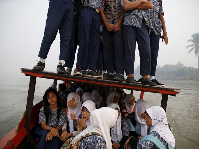 Những chiếc thuyền gỗ chòng chành như sắp chìm cũng được dùng dể đưa học sinh tới lớp ở Indonesia.