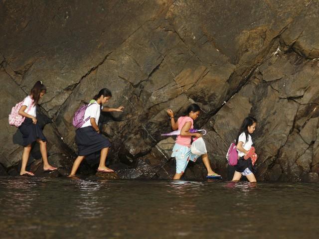 Nằm ở phía bắc Manila, các đứa trẻ ở làng Kawag, Philippines phải lội nước men theo vách đá để đến trường.