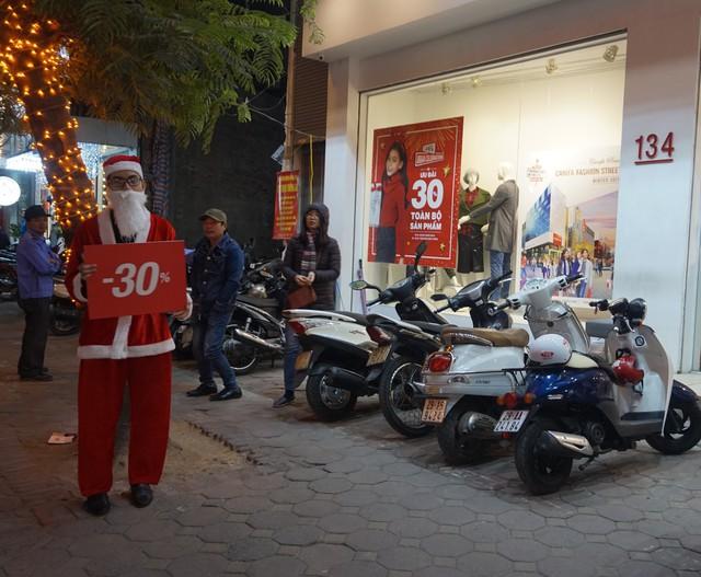 Một số cửa hàng còn thuê ông già Noel cầm biển quảng cáo thu hút người đi đường.