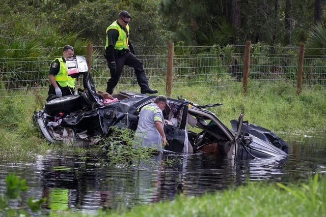 Cảnh sát đang cố gắng trục vớt một chiếc ô tô bị cơn bão nhấn chìm.