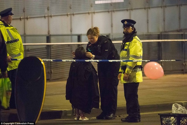 Một bé gái được cảnh sát giúp đỡ sau khi xảy vụ đánh bom kinh hoàng bên trong buổi hòa nhạc dành cho các teen người Anh.Ảnh: Cavendish Press./.