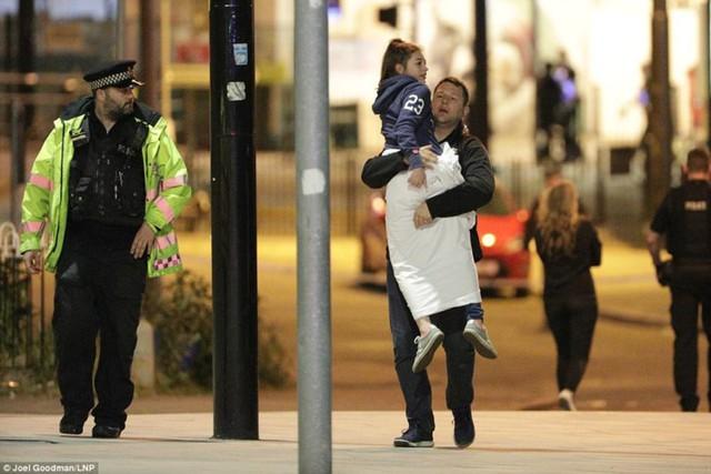 Một người cha bế con gái sau khi xảy ra vụ đánh bom khủng bố tại buổi hòa nhạc Ariana Grande. Ảnh: LNP.