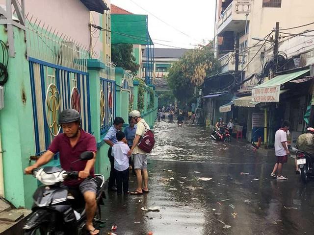 Hẻm 687 đường Kinh Dương Vương có hai trường học bị ngập khiến việc đưa đón con của phụ huynh gặp nhiều khó khăn. Ảnh: L.THOA