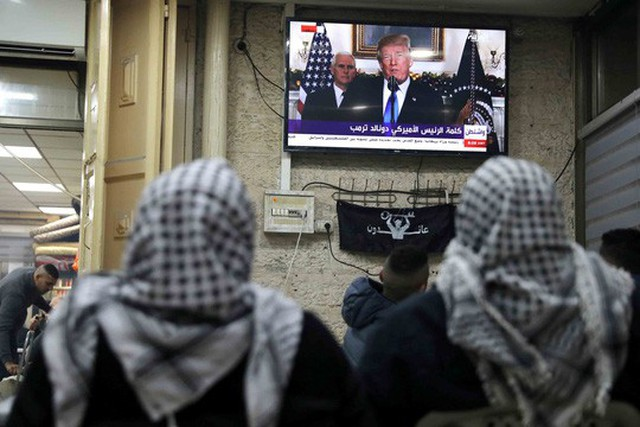 Người Palestine ở Thành Cổ tại Jerusalem xem truyền hình đưa tin về bài phát biểu của Tổng thống Mỹ Donald Trump hôm 6-12 Ảnh: REUTERS
