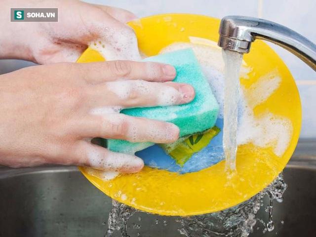 một người đang sử dụng miếng rửa bát.