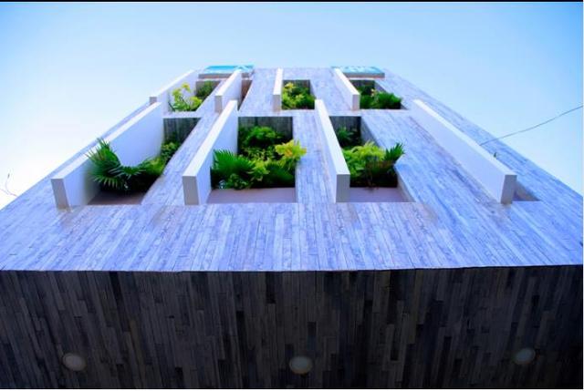 Mặt tiền ngôi nhà sử dụng bằng những tấm bê tông đúc sẵn tạo khe thoáng và không gian trồng cây xanh lọc không khí và bụi cho không gian bên trong.