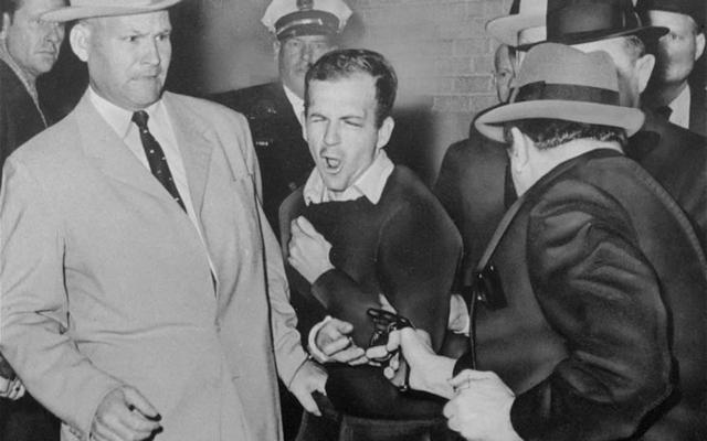Tay súng Lee Harvey Oswald (giữa), bị buộc tội ám sát Tổng thống Kennedy, bị chủ một câu lạc bộ đêm bắn chết tại trụ sở cảnh sát Dallas 2 ngày sau đó. Ảnh: AP