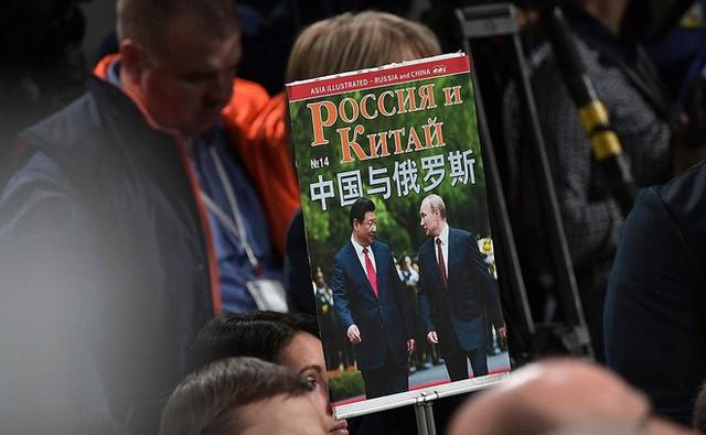 Phóng viên mang theo tấm poster tổng thống Putin và chủ tịch Trung Quốc Tập Cận Bình