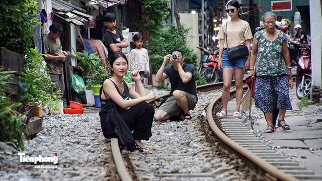 Du khách trẻ Hàn Quốc vui vẻ tạo dáng chụp hình trên các con phố ray tàu hỏa.