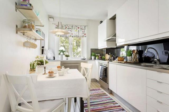 Góc bàn ăn được thiết kế tuyệt đẹp và lãng mạn có nến, bộ bàn ghế trắng muốt và cây xanh.