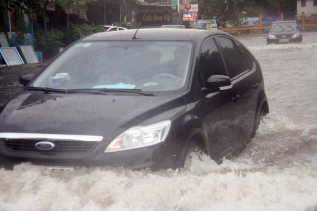 Nước ngập đến nửa bánh xe ô tô.