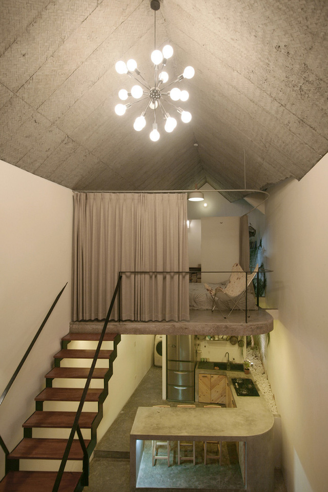 Tầng lửng được kiến trúc làm bằng bê tông trần, có góc cong tương ứng có bàn bếp bên dưới, tạo nên vẻ đẹp đồng điệu và thông thoáng cho cả ngôi nhà.