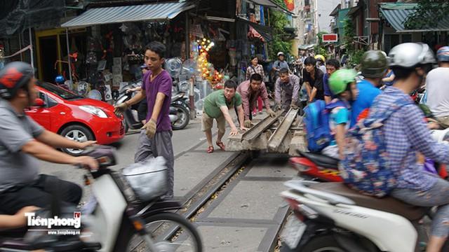 Công nhân đang vận chuyển các thanh tà vẹt mới để sửa chữa và bảo hành các con phố tàu ở khu vực trọng điểm luôn tấp nập người xe qua lại.