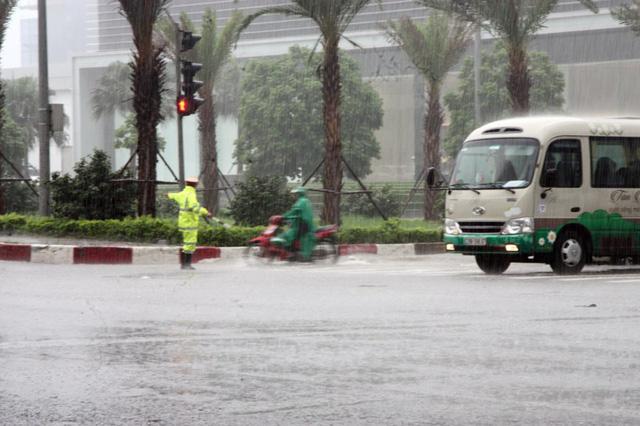 Một chiến sỹ cảnh sát giao thông đội mưa làm nhiệm vụ trên đường Phạm Hùng.