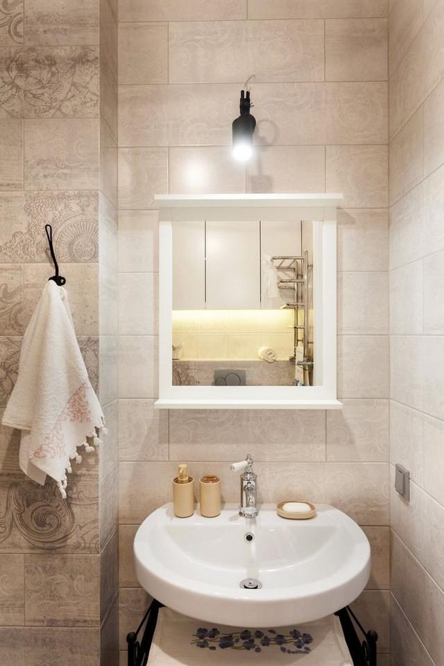 Phòng tắm tuy nhỏ nhưng được kiến trúc và bài trí linh hoạt. Bên dưới chậu rửa là kệ để đồ tiện dụng.