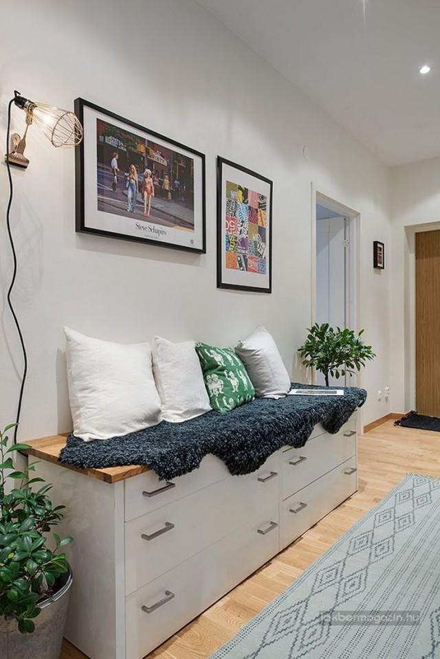 Lối vào nhà được trang trí đẹp mắt có các bức tranh treo tường và chậu cây xanh có không gian tươi mát cho ngôi nhà. Dọc tường chủ nhà còn đặt 1 hệ tủ kệ đa năng làm nơi trữ đồ hoàn hảo.