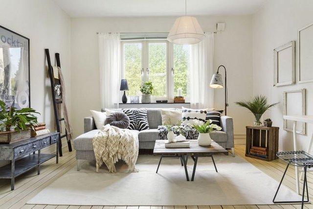 Không gian phòng khách nhỏ chào đón người vào có chiếc sofa xám và bàn trà xinh xắn.