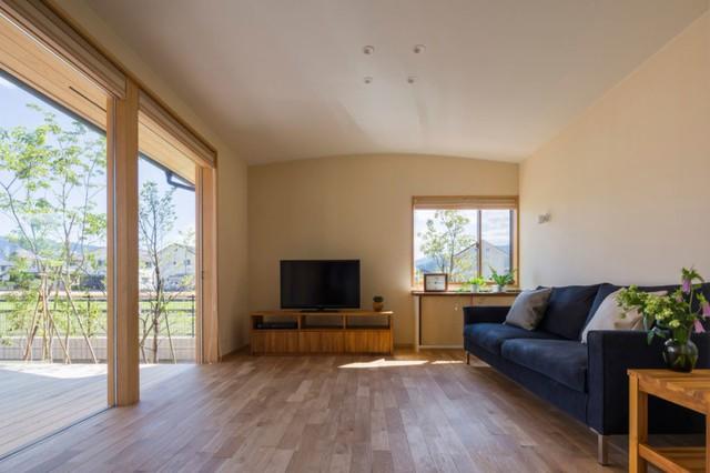 Phòng khách rộng rãi thoáng mát được kiến trúc gọn gàng có ghế sofa kê dọc bức tường. Từ phòng khách có thể nhìn ra dao động sân rộng thoáng trồng nhiều cây xanh phía ngoài.