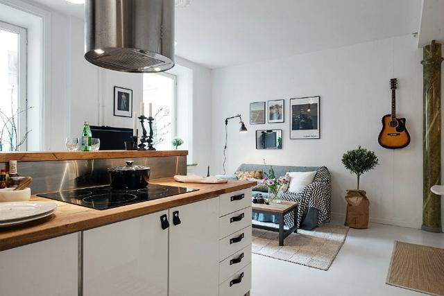 Tô điểm cho không gian phòng khách là cây xanh, chiếc đàn ghita và những bức tranh treo tường. Góc nhỏ này được phối hợp nhẹ nhàng giữa tông màu trắng và xanh lam tạo nên cảm giác mát mẻ, thoải mái vô cùng.
