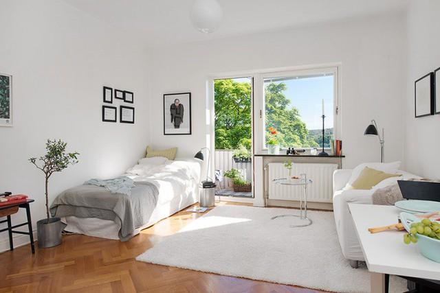 Khu vực phòng khách ấm cúng với ghế sofa êm ái, thoải mái đi kèm chiếc bàn cà phê có cấu trúc nhỏ nhắn và lạ mắt. Phòng khách được bố trí ở góc căn hộ, bên cạnh giường ngủ.