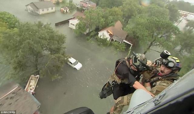 Cứu hộ trực thăng Mỹ, Sea Combat Squadron 7 đang trèo vào một ngôi nhà bị tàn phá sau bão, đường phố Beaumont đã bị ngập lụt nặng nề.