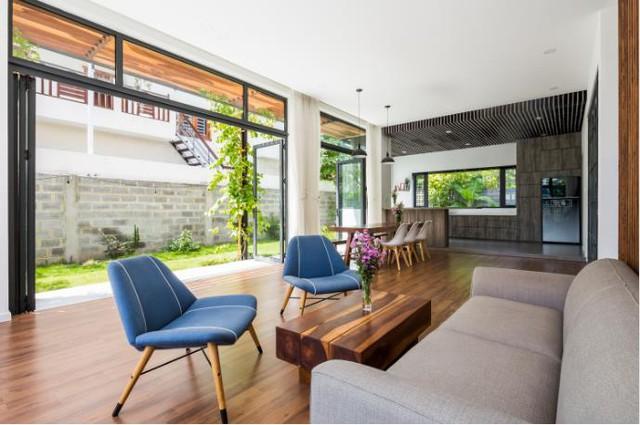 Góc tiếp khách được thiết kế đơn giản, nhẹ nhàng với tầm nhìn ra khu vườn xanh mát chạy dọc hông nhà.