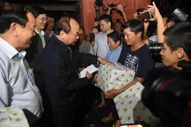 Thủ tướng Nguyễn Xuân Phúc trao quà, động viên người dân. Ảnh VGP/Quang Hiếu