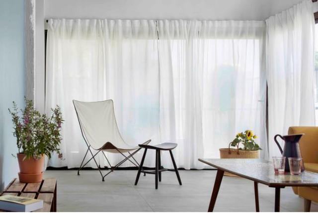 Khu vực sát cửa sổ chủ nhà chỉ dành làm không gian thư giãn tuyệt đẹp có chiếc ghế bành cách điệu và hoa tươi. Không gian phòng khách tuy bé nhưng nhờ được kiến trúc có tông màu trắng chủ đạo khiến không gian khi nào cũng thoáng sáng và rộng rãi.