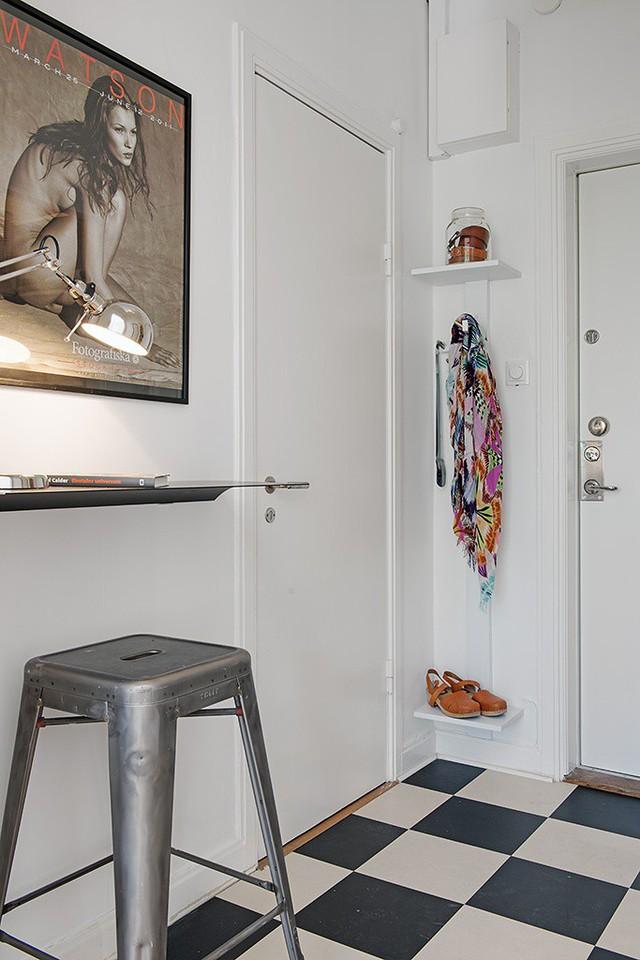 Vì diện tích có hạn nên lối vào nhà được bài trí khéo léo và tận dụng tối đa góc tường để trữ đồ. Ngay bên cạnh là một chiếc bàn làm việc nhỏ xinh được gắn cố định vào tường.