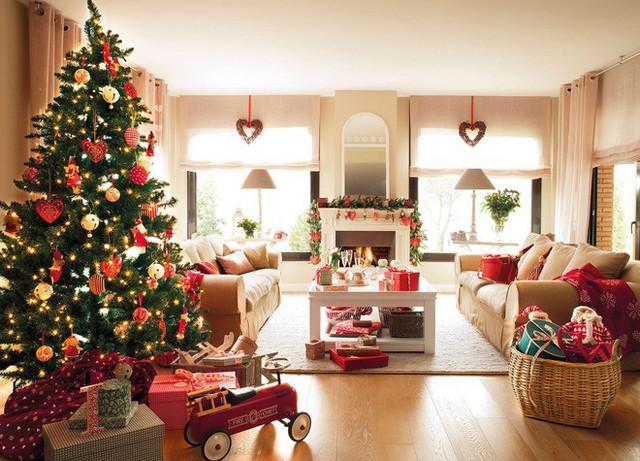 Ngoài cây thông Noel lung linh thì phòng khách rộng lớn này còn được trang trí rất nhiều tiểu tiết khác như những trái tim treo đối xứng hai bên cửa sổ, dây kết bằng lá thông quanh lò sưởi..