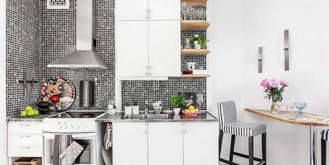 Một mảng tường kết hợp đan xen hai tông màu đen trắng nơi bếp nấu có chức năng đặc biệt giúp phân chia không gian với khu vực ăn uống bên cạnh.