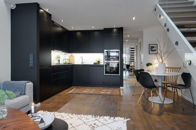 Tuy được bố trí trong cộng 1 không gian mở có phòng khách nhưng khu vực bếp ăn lại gây ấn tượng đặc thù và được phân chia rạch ròi bởi 1 hệ kệ tủ tông màu đen cao sát trần.