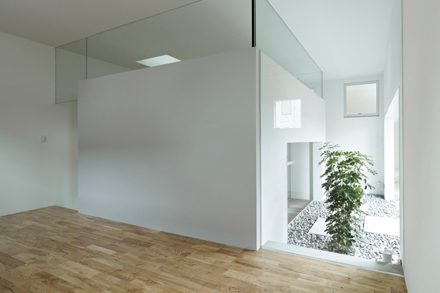 Không gian phòng ngủ lớn tầng 1 thoáng sáng với sàn nhà được lát gỗ.