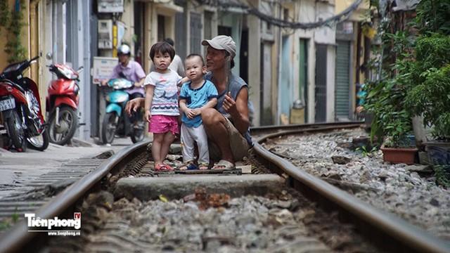 Đường tàu cũng là sân chơi, nơi nghỉ ngơi của người già và trẻ nhỏ sống quanh đấy.