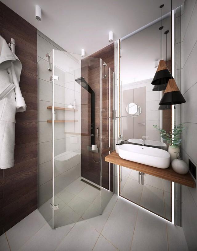 Xung quanh phòng tắm đứng là hệ cửa kính tạo sự thông thoáng cho không gian. Một chiếc gương lớn cũng góp phần nhân đôi diện tích cho góc nhỏ này.
