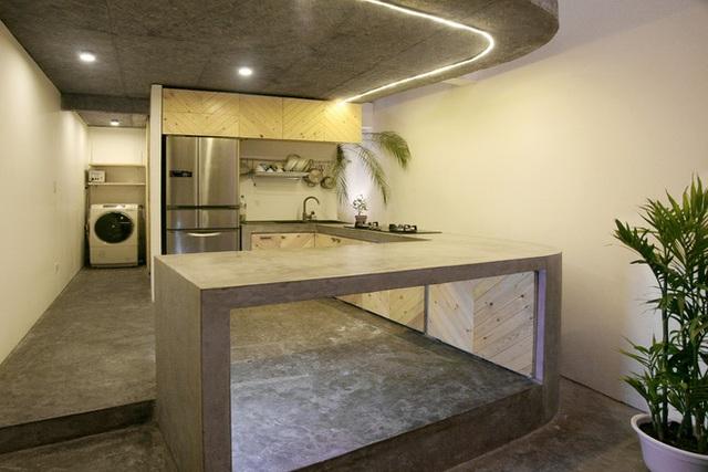 Không gian bếp ăn thoáng mát có bàn bếp được xây cố định bằng bê tông, phủ nước xi măng sáng lạnh.