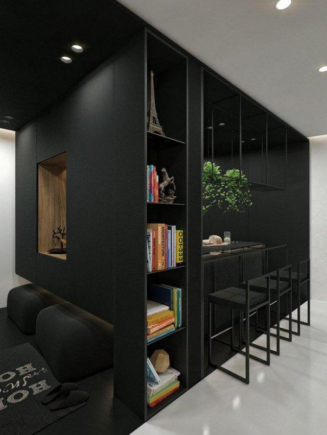 Góc bếp nhỏ là 1 khối tủ màu đen đa năng có 1 bên là khu vực bếp và bàn ăn, 1 bên là các kệ có vai trò như 1 giá sách và góc trang trí nhỏ.
