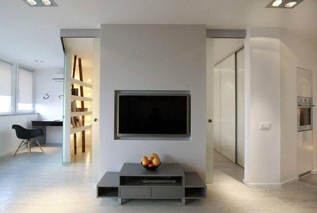Trên bức tường nhỏ là chiếc ti vi màn hình rộng được gắn chặt vào tường để tiết kiệm diện tích và mang lại không gian thông thoáng cho phòng khách.