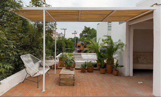 Khoảng sân vườn tuyệt đẹp có điểm nhấn hút mắt là mái che bằng hệ gỗ lam cộng chiếc ghế bành xinh xắn và rất nhiều cây xanh.